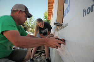 Swinging nail guns and using chop saws, father daughter build home together